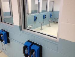 Foreground phones affixed to wall, mid-ground glass window, background room with phones affixed to wall, each with stool